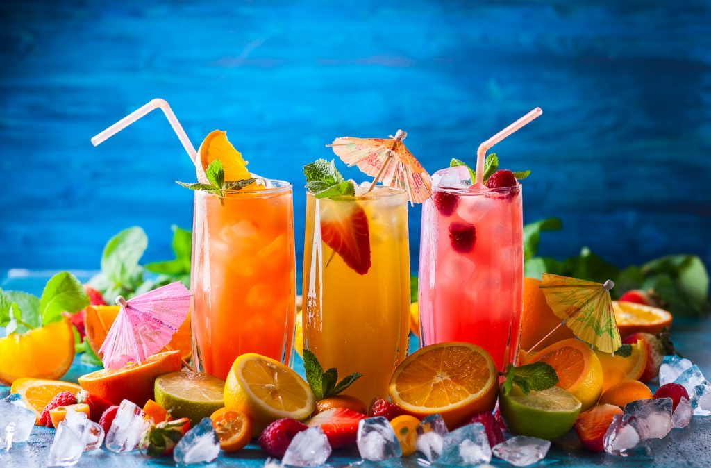 Different types of summer drinks in glasses, cubes of ice and slice of fruits  on blue table. Health